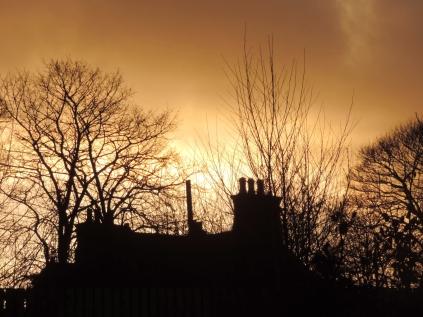 Sunset behind an old farmhouse